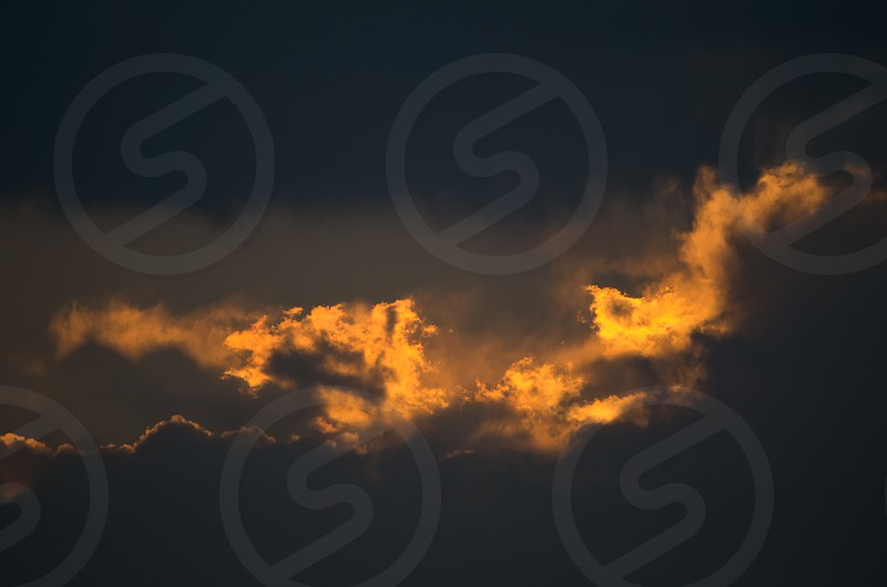 Dark Cloudscape Closeup at Sunset with Flames photo
