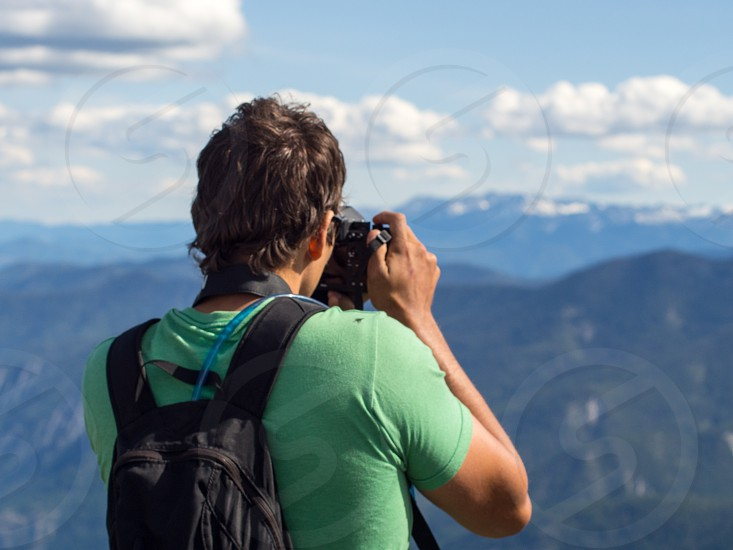 Man taking photo of mountains in North Cascades WA photo