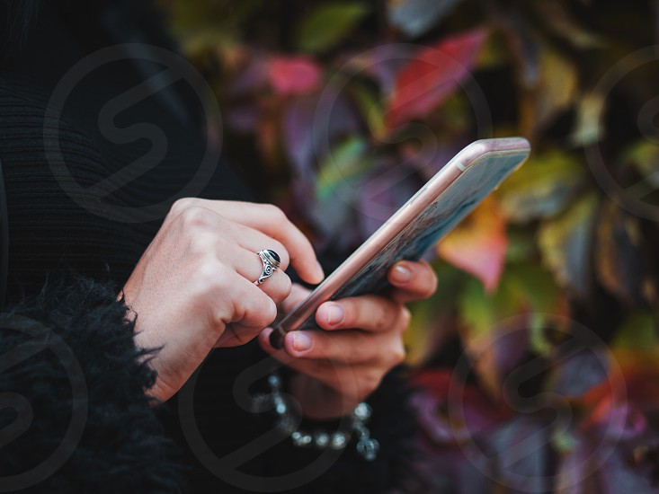 Beautiful young hipster woman using smart phone in autumn park. Hands with bracelets and ring. photo