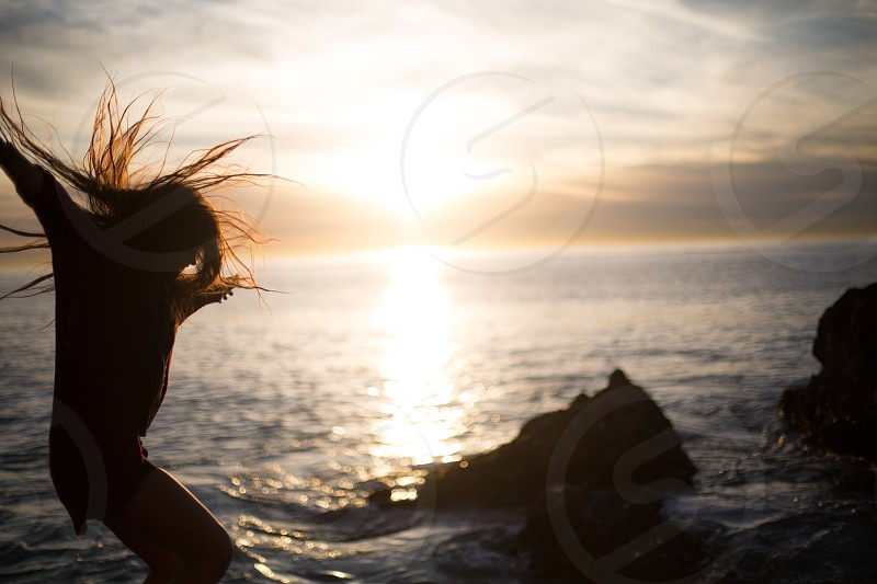 woman jumping on seashore and sea view photo