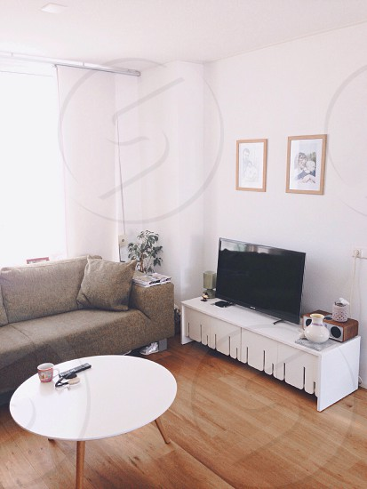 black flat screen tv on white wooden rack against white painted wall photo