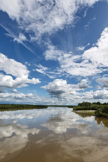 Beautiful summer landscape: view on Kamchatka River beautiful clouds and reflection in water. Russia Far East Kamchatka Peninsula. photo