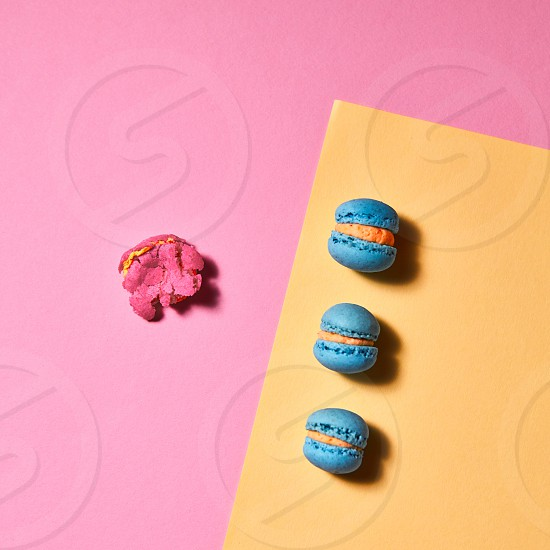 Colorful composition of macaroons. On a yellow pink paper background whole blue macaroons and one broken macaroon with a reflection of shadows. Top view photo