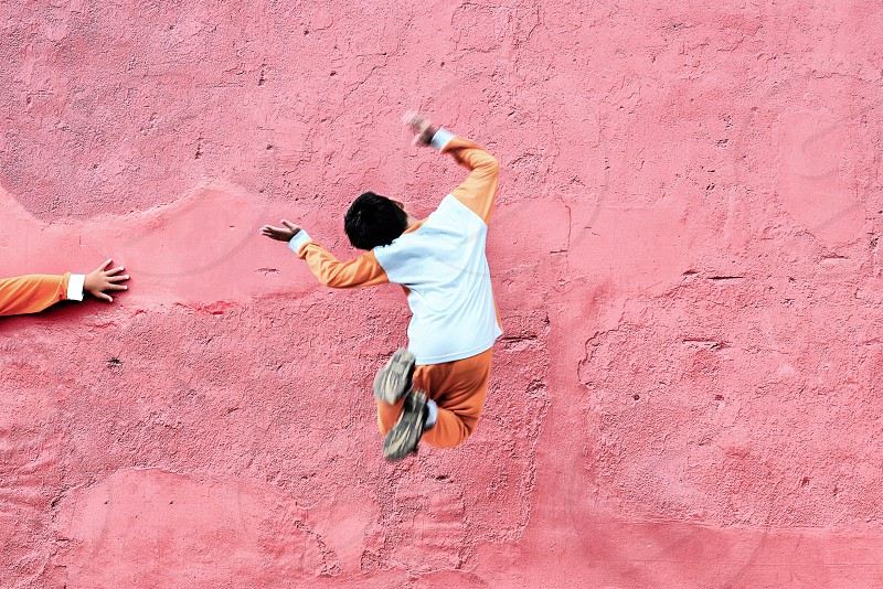 boy jumping against a pink wall photo