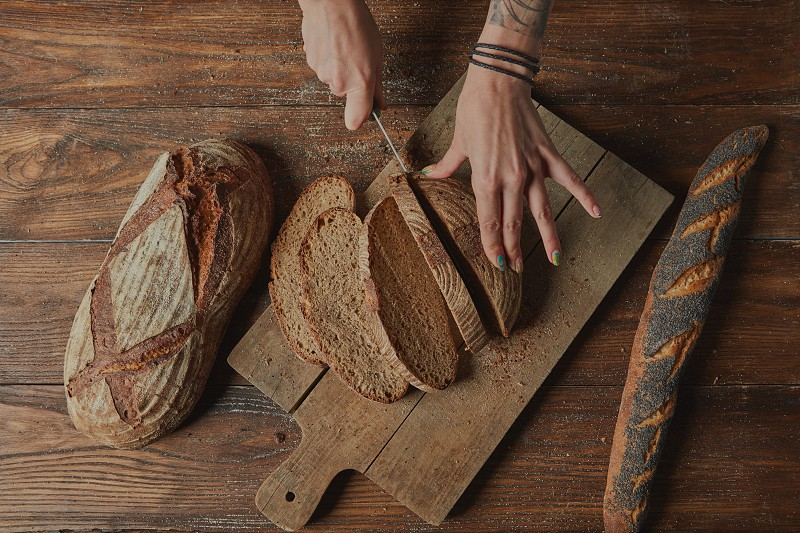 Male hands slicing bread on brown wooden background Flat lay photo