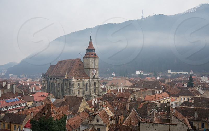 Panoramic  view of Brasov old town and Black Church with the Carpathian Mountains in a foggy winter day. Transylvania Romania photo