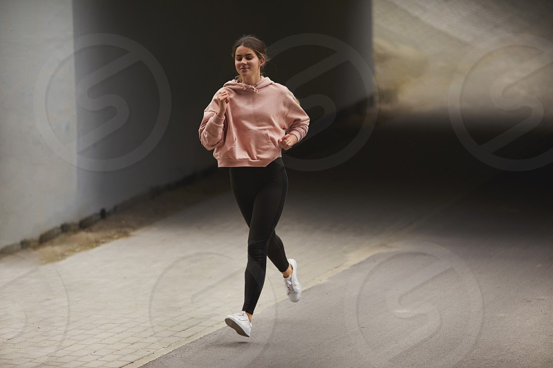 Sporty girl run on the street with night city baclkground photo