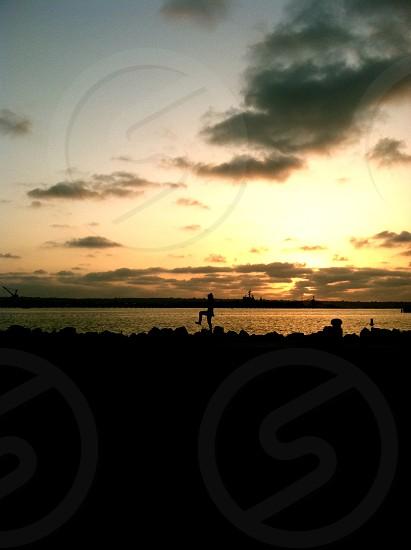 man behind sun setting near ocean photo