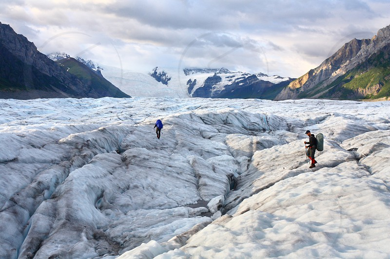 Backpackers crossing the Root Glacier in Wrangell-St.Elias National Park Alaska. The Stairway Icefall is in the distance. photo