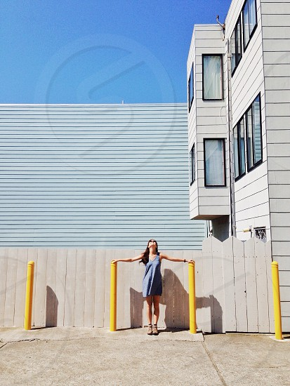 woman standing holding yellow poles photo