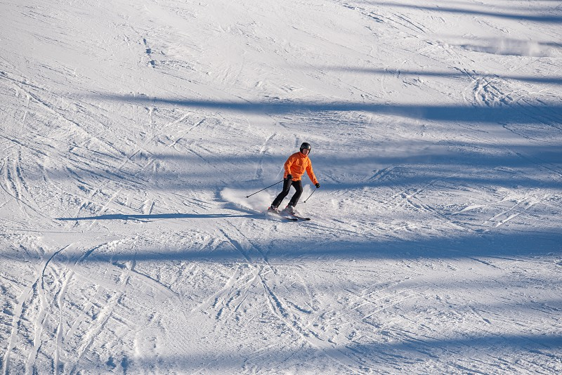 A skier descends a hill in the mountains. photo