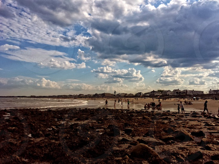 group of people walking on brown sand near seashore under white clouds and blue sku photo