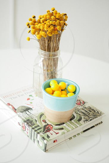 flowers tomatoes book vase glass table white yellow home decor blue clean interior natural light  photo
