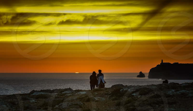 Two peple watching the summer sunset on Saint Vincent Cape Algarve Portugal photo