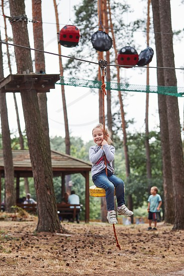 Happy girl riding on the zip line in rope park in forest while spending summer vacation. Real people authentic situations photo