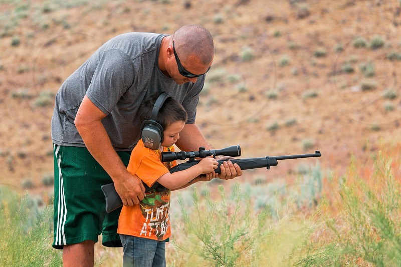 Father and son bonding firearm target practice hunting  photo