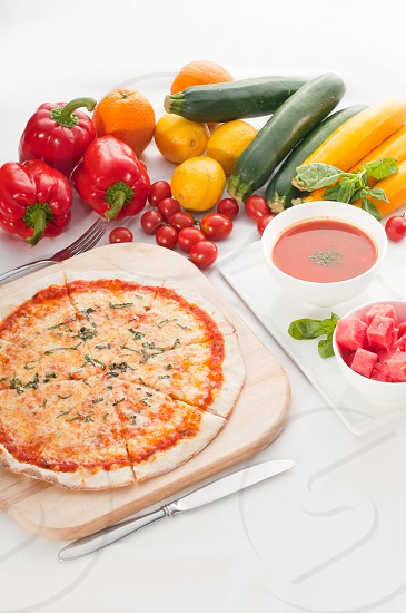 Italian original thin crust pizza Margherita with gazpacho soup and watermelon on sideand vegetables on background photo