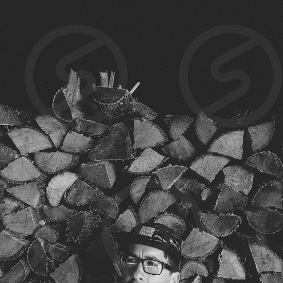 black and white image of man in glasses with chopped wood background photo