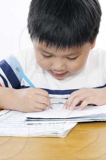 Closeup portrait of young kid doing schoolwork photo