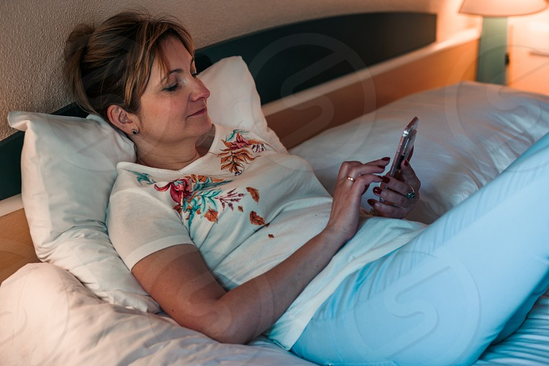 Young woman using smartphone while laying in bed in bedroom photo