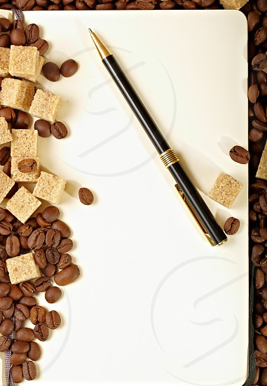 Coffee beans on paper with pen background. Natural morning light. photo