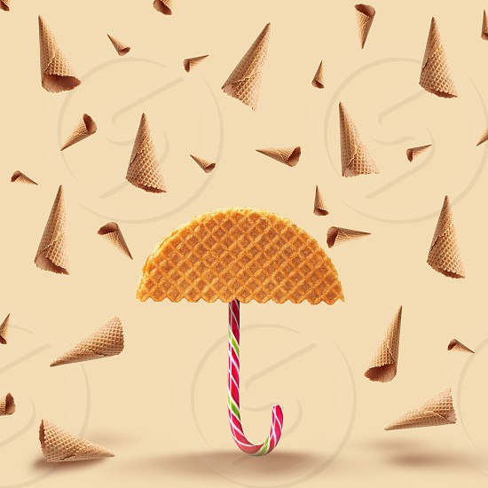 Umbrella made of waffle and waffle cones of rain on a yellow background. photo