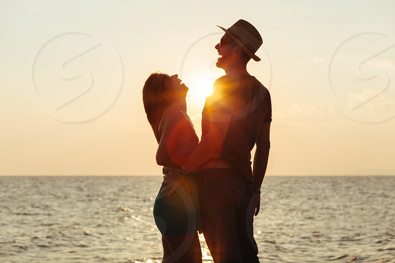 Young couple in love enjoying sunset on the beach photo