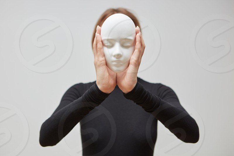 Young girl in a black sweater hold plaster mask sculpture instead of face on a white background place for text. Concept The masks we wear. photo