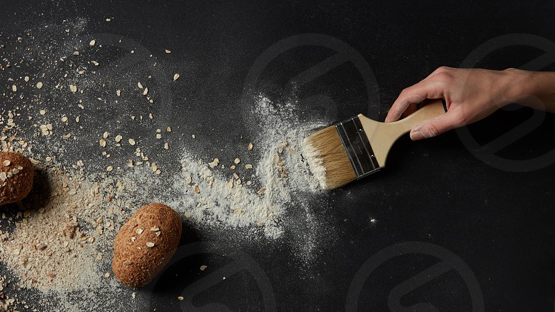 Someone sweeping flour with brush over black background. Several buns represented on table. Cooking process concept. photo