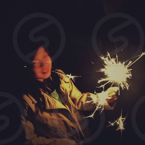 woman wearing beige coat holding lighted up sparkler during nighttime photo