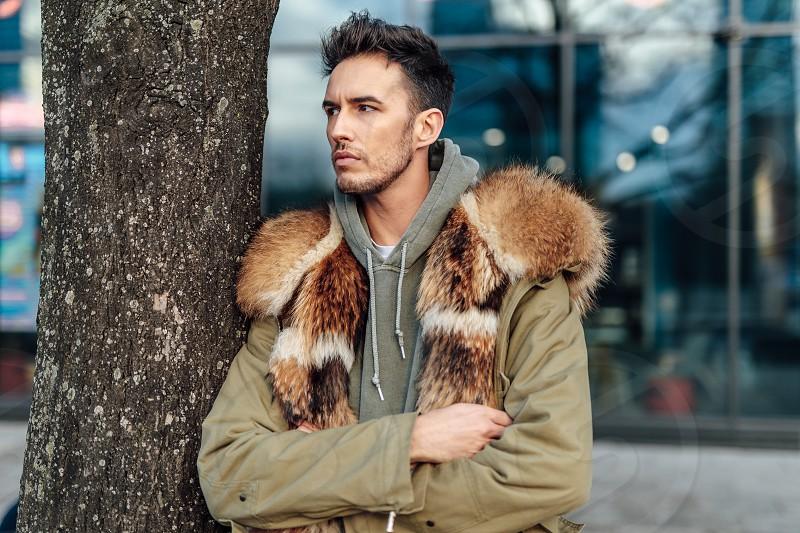 Fashionable man walk outdoors wear  fur jacket with street background - Image photo