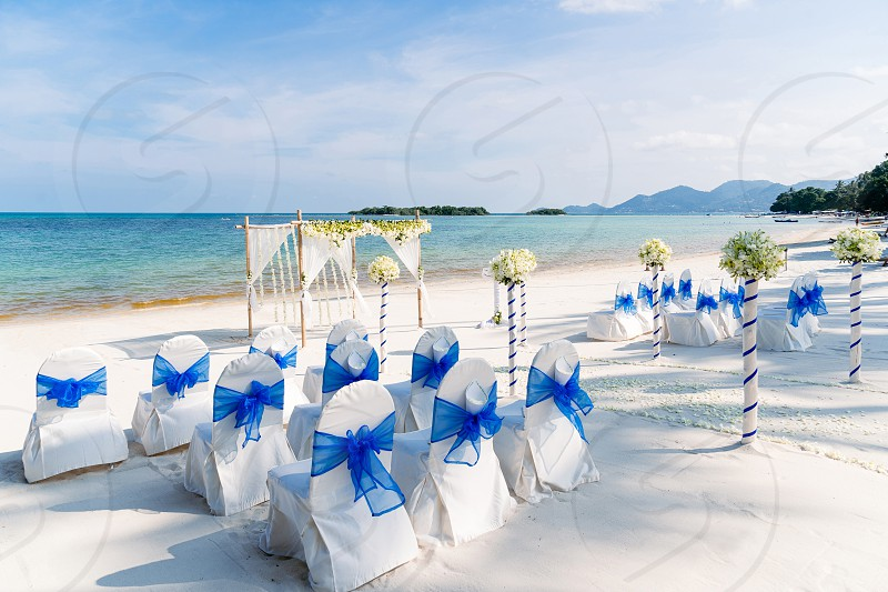 Beautiful destination wedding venue setting on the beach white cover chairs with blue organza sash flower decoration on arch altar and aisle. Panoramic ocean view photo