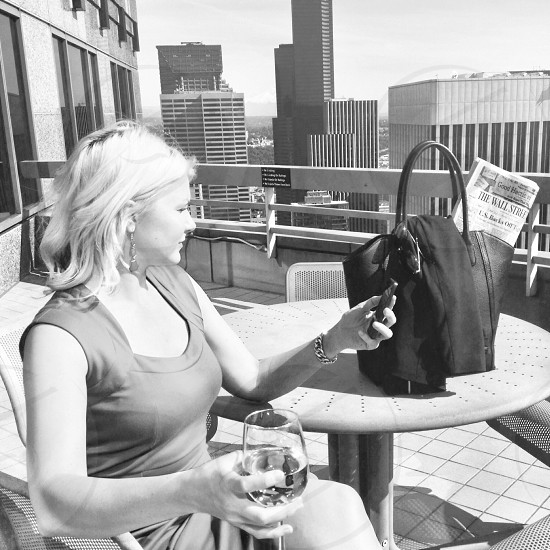 woman holding wine glass on skyscraper photo