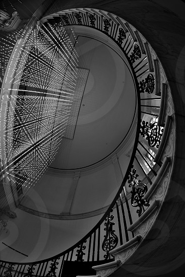 greyscale low angle photography of spiral stairs of concrete building photo