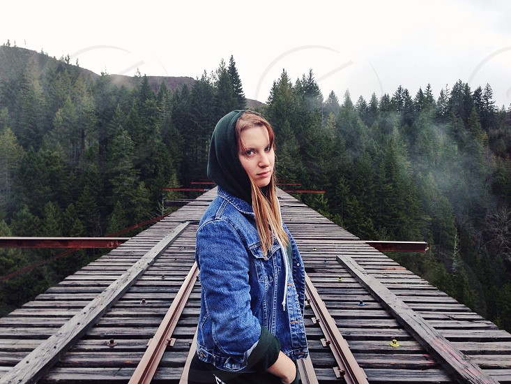 woman in denim jacket standing on top of train trestle photo