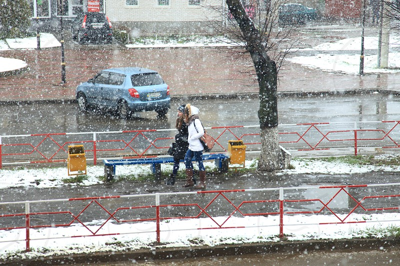 2 person walking on the walkway with blue hatchback park beside with a snowy weather during daytime photo