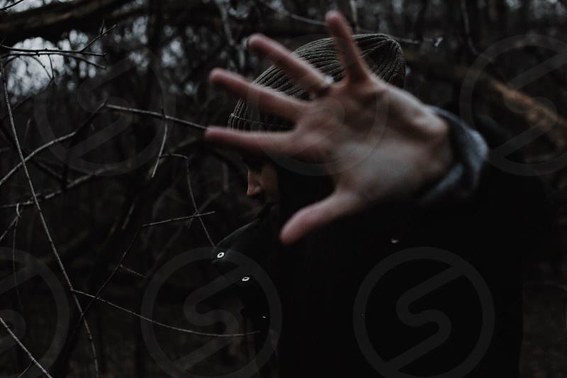 a woman wearing brown knitted cap and jacket in a forest with her palms in the air photo