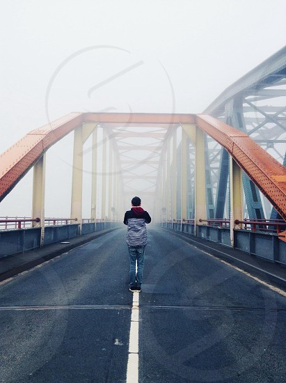 man in black and gray striped hoodie and blue jeans on fog covered bridge photo