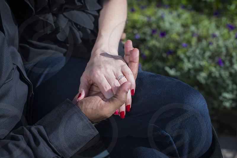 Guy holding Girls hand while sitting. photo