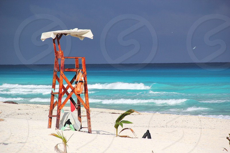 brown wooden lifeguard chair on white sand beach photo