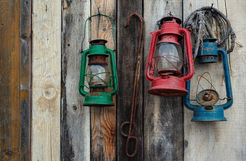 Details of an old wooden wall with three lanterns painted in different vivid colors hanged. photo