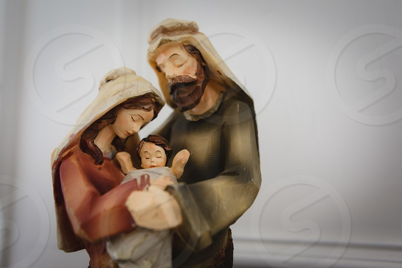 The Holy Family wood sculpture near white painted panel photo