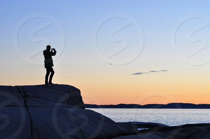 man standing on a rock formation taking picture photo