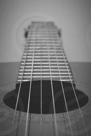 gray-scale photograph of six-string acoustic guitar photo