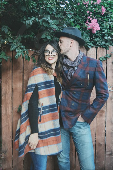 man wearing brown and blue checked double breasted coat and black fedora hat kissing the head of woman wearing black long sleeve shirt with brown white and blue poncho photo