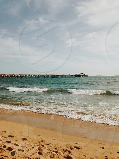 grey and white cloudy sky over pier in teal ocean water with brown sandy shore photo
