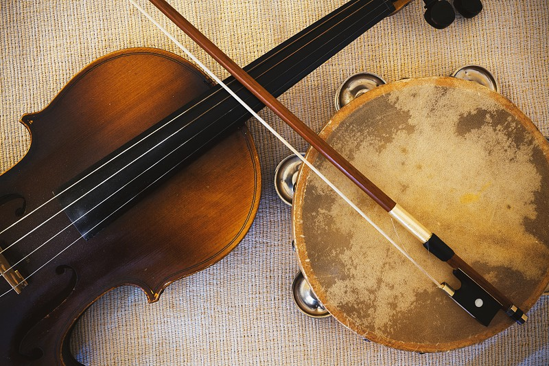 Details of an old and dusty violin from Czechoslovakia and tambourine.  photo