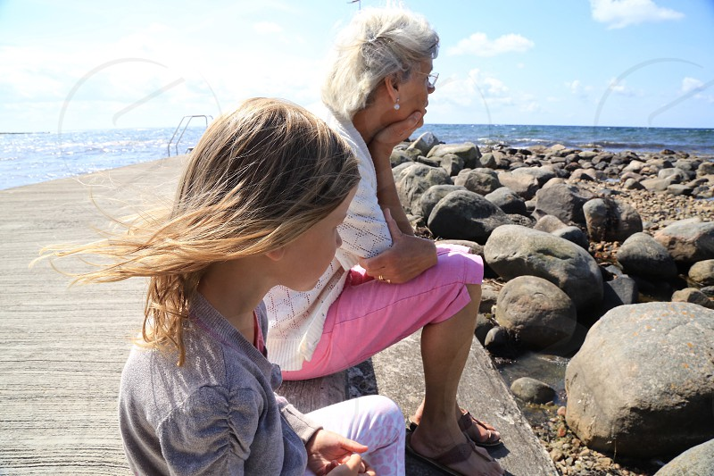 Grandmother  granddaughter  summer sea rocks  beach  togetherness  tranquil  thoughtful  photo