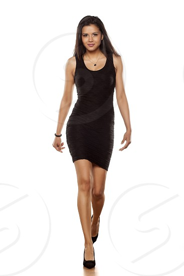 young beautiful lady walking in short black tight dress photo