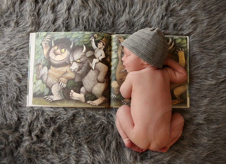 """Newborn baby boy in beanie hat on top of """"Where The Wild Things Are"""" book. photo"""